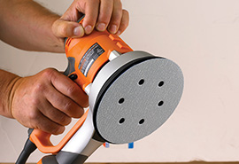 An orbital sander with a vacuum paper disc attached