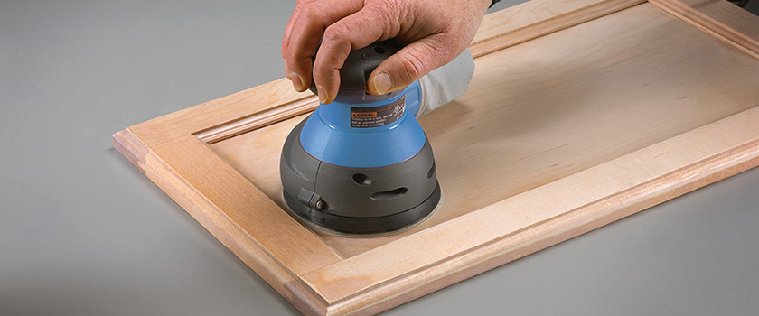Using A Palm Sander To Remove Old Finish From Kitchen Cupboards