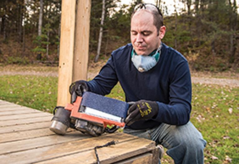 Replacing an abrasive belt on a portable belt sander