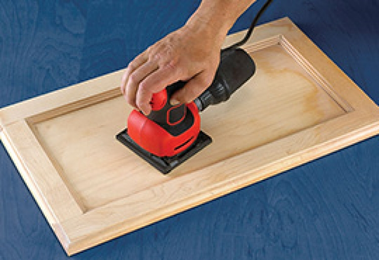 Using an orbital sander to remove old finish from kitchen cupboards