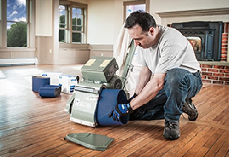 Installing an abrasive sanding belt on a floor sander