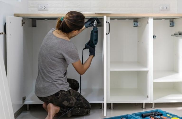 Femme démontant des portes de cuisine