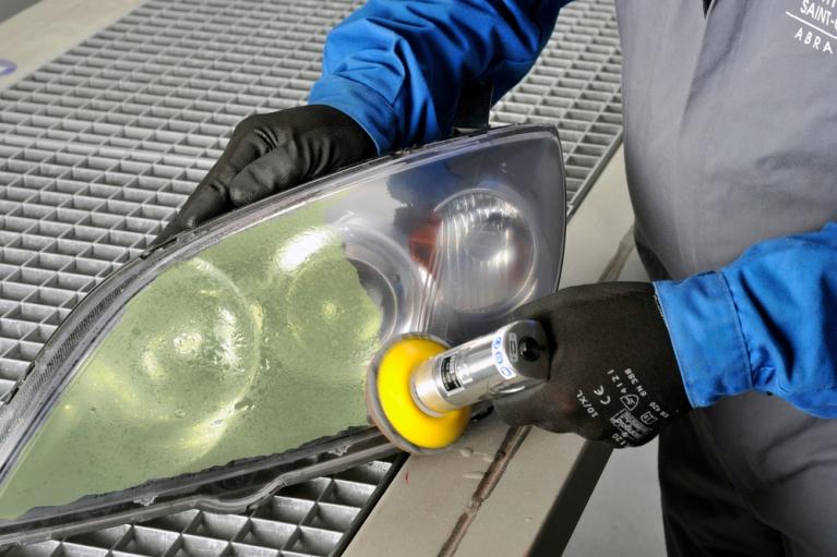 mężczyzna odnawia reflektor samochodowy