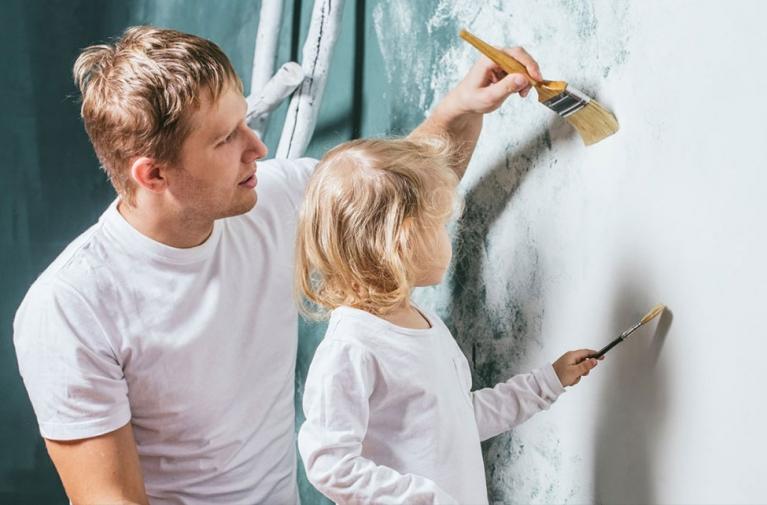 Mężczyzna z córką malują ścianę