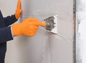 Applying drywall compound over a taped seam