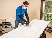 Sanding an exterior door as part of the preparation required prior to painting