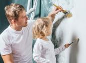 Man och dotter målar en vägg