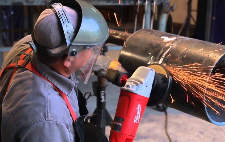 grinding a weld from metal pipe